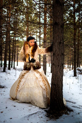 Girl in a ball gown and coat in the Park and in the woods