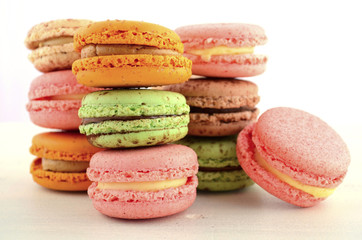 Colorful macaroons on white wood table.