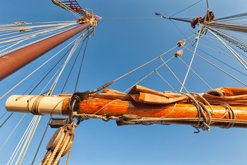 Tall ship masts and rigging against blue sky. Looking up