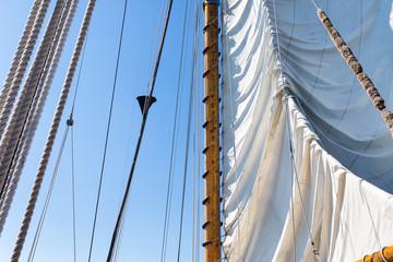 Tall ship raising the sail against a clear blue sky