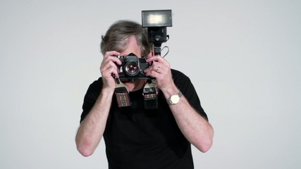 Photographer directing while taking pictures in studio with SLR and flash.