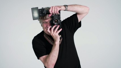 Photographer taking pictures in studio with SLR and flash.