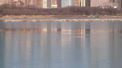 Chicago, Illinois skyline reflecting on Lake Michigan icy water