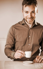 Smiling happy man enjoying a cup of coffee