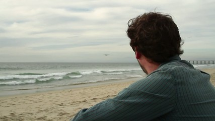 Close up of a man sitting on the beach, watching the Pacific Ocean.