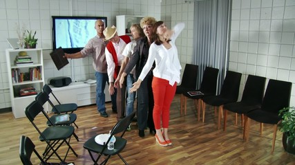 Five actors, men and women of various ages, practice while waiting for an audition for a musical.