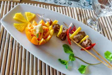 orange and pineapple appetizer served on plate in restaurant or