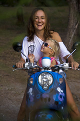 Mama and little daughter riding motobike