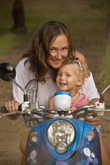 Mama and cute little daughter riding motobike
