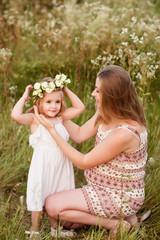 Молодая мама одевает венок из роз дочке поправляя прическу