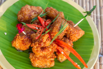 chicken fried in honey sauce, meat ball served on palm tree leaf