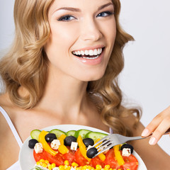 Portrait of young woman with vegetarian salad, on grey