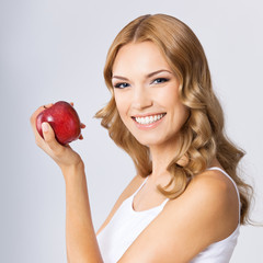 Young woman with red apple, over grey
