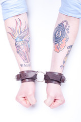 Tattooed Arms/tattooed arms with leather handcuffs on wrists