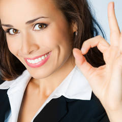 Happy business woman with okay gesture, on blue