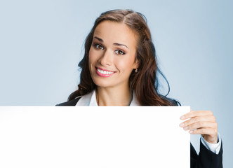 Businesswoman showing signboard, on blue