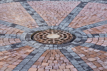 Manhole on paving tiles