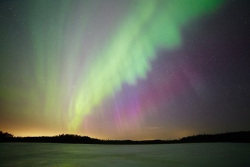 Aurora borealis - Northern lights above the lake in the winter
