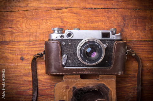 Leinwanddruck Bild Retro camera on wood table background, vintage color tone