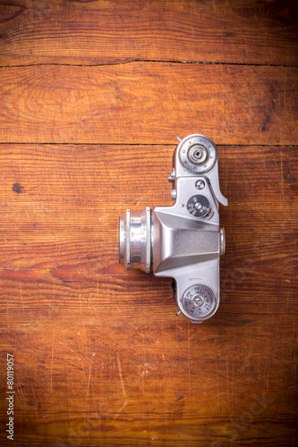 Leinwanddruck Bild Vintage photo camera on a wooden background, top view