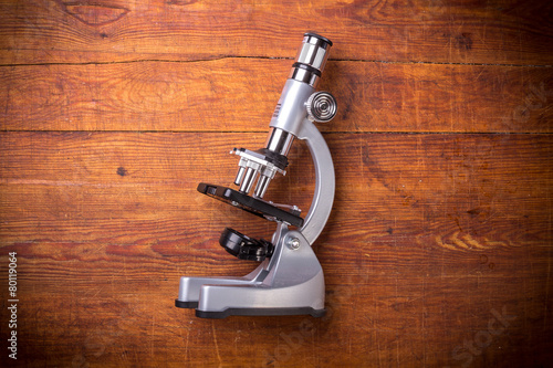 Leinwanddruck Bild Microscope on table for vintage science background