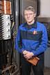 Senior man electrician in uniform stands near high voltage box