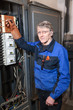 Electrician repairman in uniform stands near high voltage box