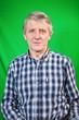 Half length portrait of senior Caucasian man, green background