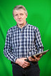 Senior Caucasian man with tablet in hands, green background