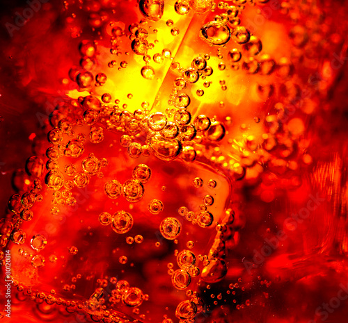 Cola background. Cola with Ice and bubbles in glass closeup