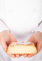 Rustic handmade gourmet cheese in the hands of the cook