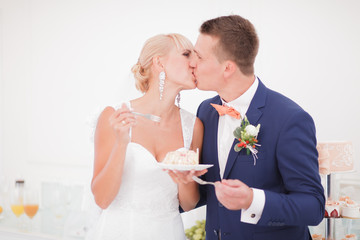 the bride and groom eat the cake