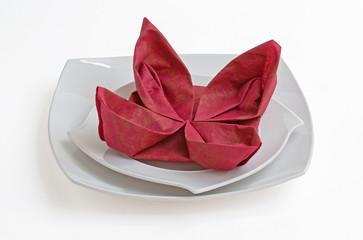 Pliage de serviette papier grenat en fleur sur assiette blanche