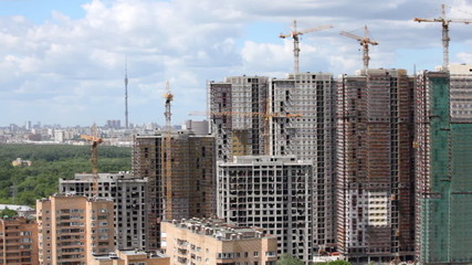panorama of complex of buildings under construction against city landscape