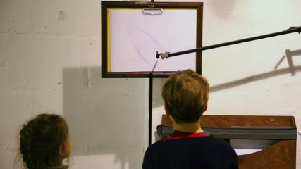 Two kids watch how piece of paper sways and pen draws