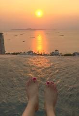 feet on poolside meet sunset.