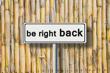 Be right back written on road sign against a bamboo fence