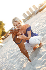 Young woman having fun on the beach with  small dog
