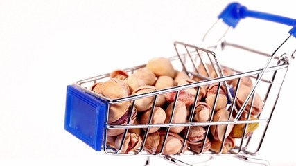 Small shopping cart with pistachios spins, closeup isolated