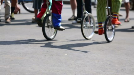 Feet of clowns in colored clothes riding on unicycles outdoor