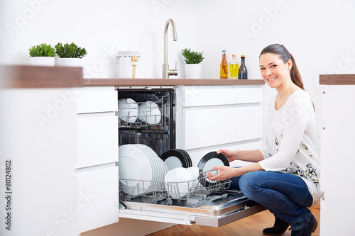 20s woman in kitchen, empty out the dishwasher 2 - 80124802