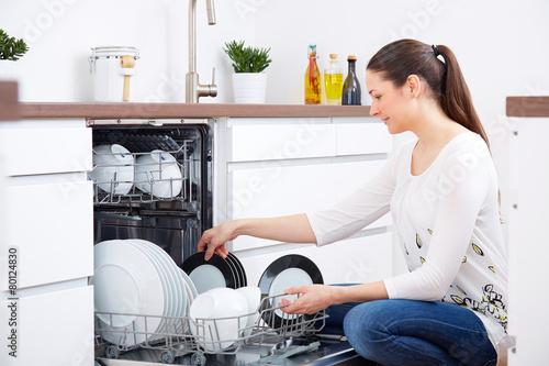 Leinwanddruck Bild 20s woman in kitchen, empty out the dishwasher