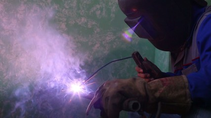 Welder in protective suit and mask welds metal pipes.