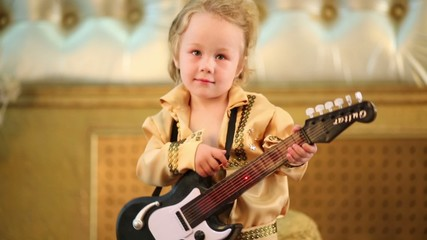 Cute little boy in pop retro costume with guitar toy
