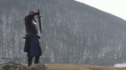 Soldier drawing sword on mountain