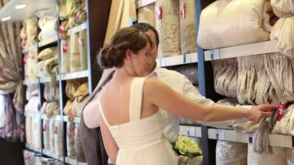 newly married couple choose bedding in store, looks at blanket