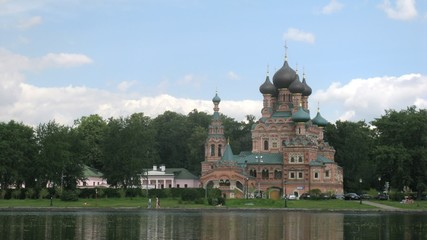 Temple of Trinity stands near river against blue sky in Ostankino, time lapse