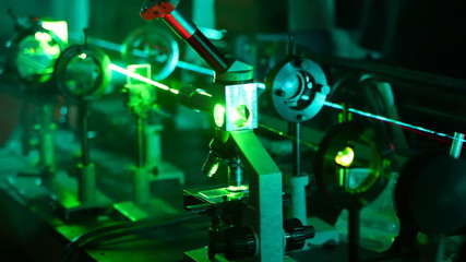 complex of magnifying glasses and microscope with green laser flashing in smoke