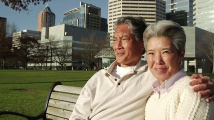 Older Asian-American man and woman sitting on a park bench with the city of Portland, Oregon in the background.  Two medium close ups with dolly movement and tilt from trees.