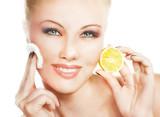 Young woman applying lemon facial mask
